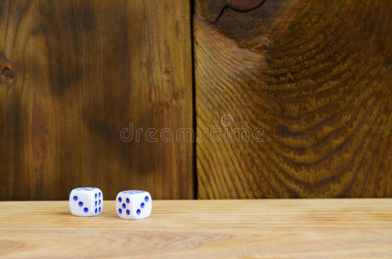 A few dice lies on the surface of natural wood. Items for generating numbers from one to six in the form of points that are paint stock image