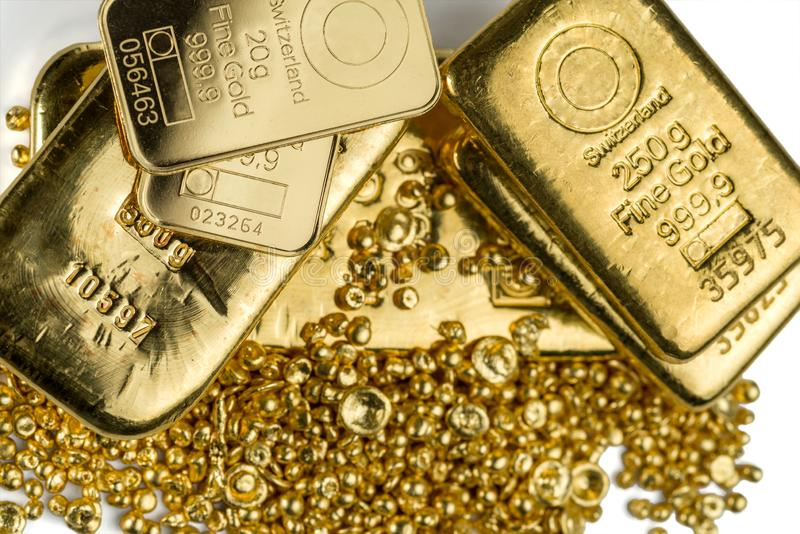 A few different gold bar on a pile of gold granules. stock photo