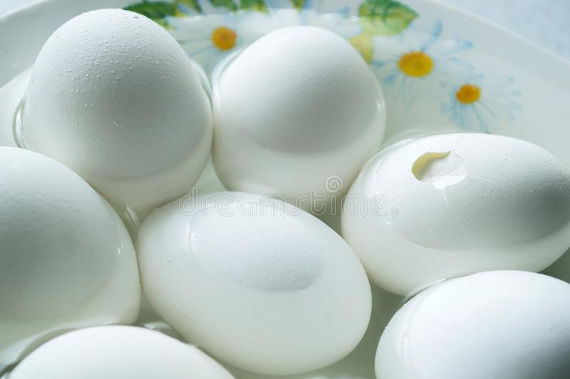 A few eggs in the water on the plate stock image