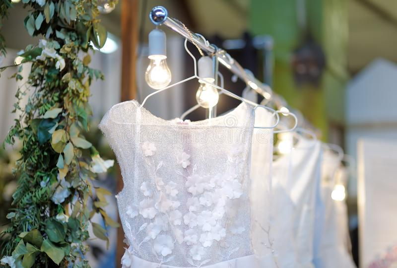 Few elegant wedding, bridesmaid ,evening, ball gown or prom dresses on a hanger in a bridal shop. Fashion for beautiful brides royalty free stock photos