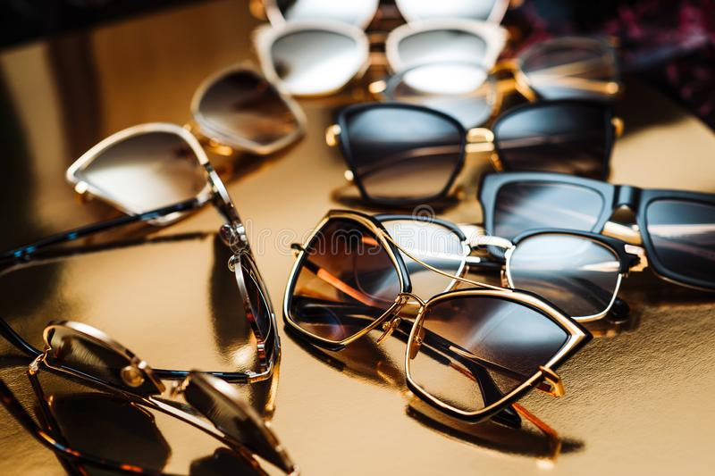 A few elite Sunglasses in a modern fashionable frame on a gold background stock image