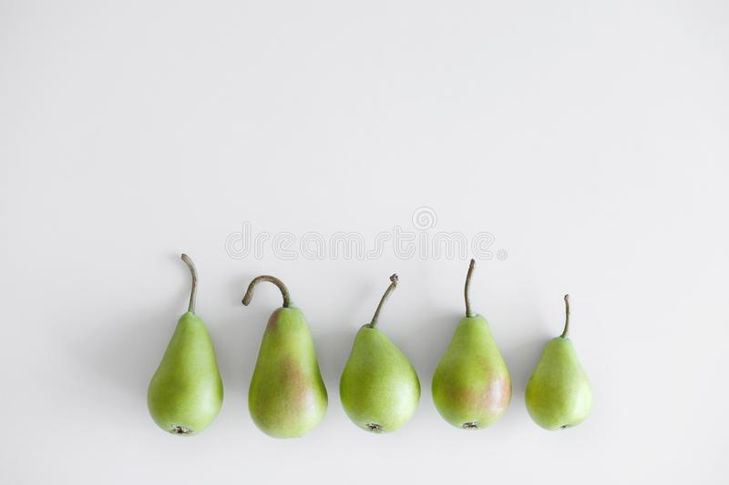 Five objects of green pears with twigs lie in a row on a white background. Different form, conceptuality. A few five green yellow pears lie a pile on a white royalty free stock photography