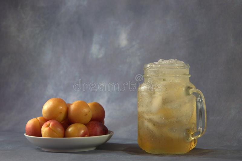 A few fresh apricots on a plate and a cup of apricot juice with ice. Close-up stock photography
