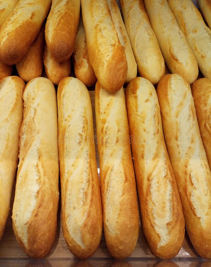 A few fresh baked baguettes. Bread in the supermarket, vertical photo stock images