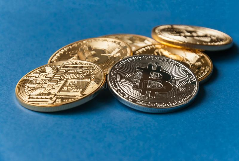 A few gold and silver coins bitcoin lie on a blue backgroundConcept of crypto currency. stock photo