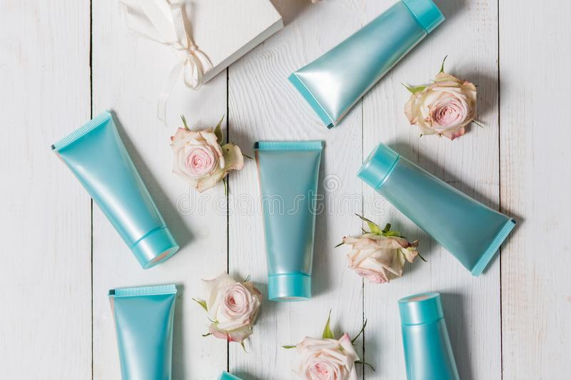A few of the hand cream, primer, toner, face in blue, turquoise packing on a white wooden background with flowers of roses, overhe stock images