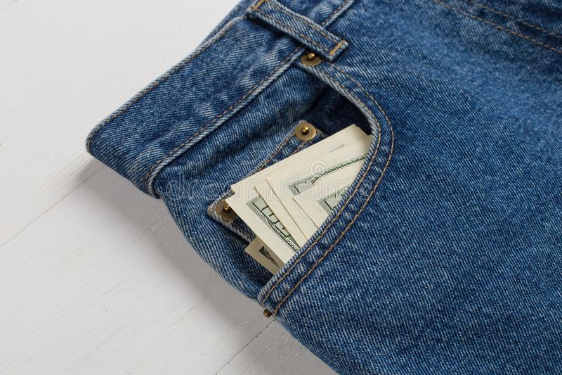 A few hundred dollars banknotes in a jeans pocket. The concept of wealth and salary for work. A few hundred dollars banknotes in jeans pocket. The concept of royalty free stock photo