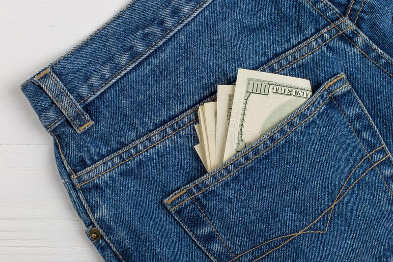 A few hundred dollars banknotes in a jeans pocket. The concept of wealth and salary for work. A few hundred dollars banknotes in jeans pocket. The concept of stock photos
