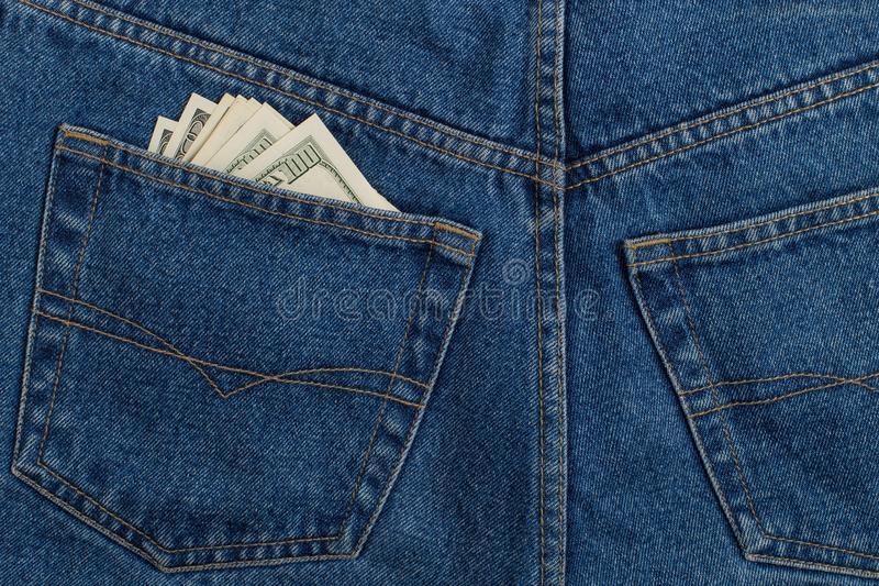 A few hundred dollars banknotes in a jeans pocket. The concept of wealth and salary for work. A few hundred dollars banknotes in jeans pocket. The concept of royalty free stock photography