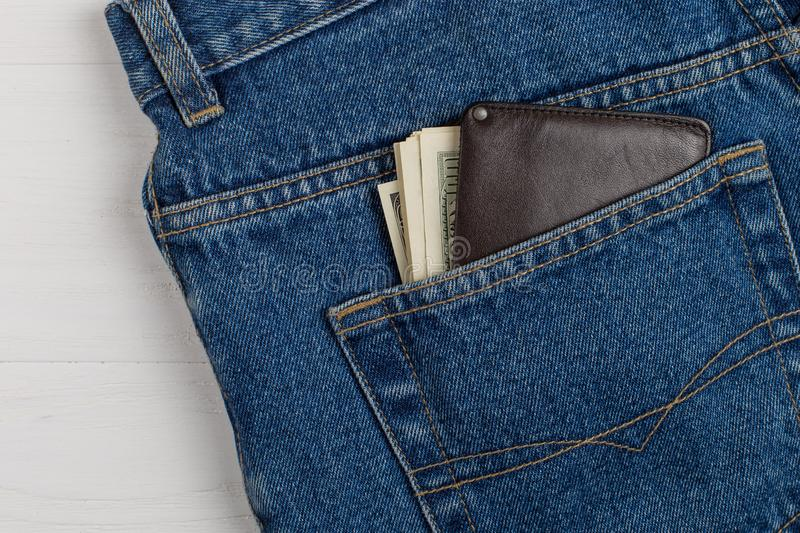 A few hundred dollars banknotes in a jeans pocket in your wallet. The concept of wealth and salary for work. A few hundred dollars banknotes in jeans pocket in stock photos