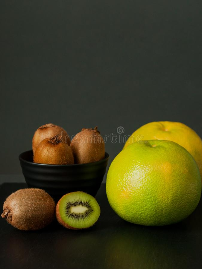 Few kiwi in black plate and sweetie still life on dark background. royalty free stock image