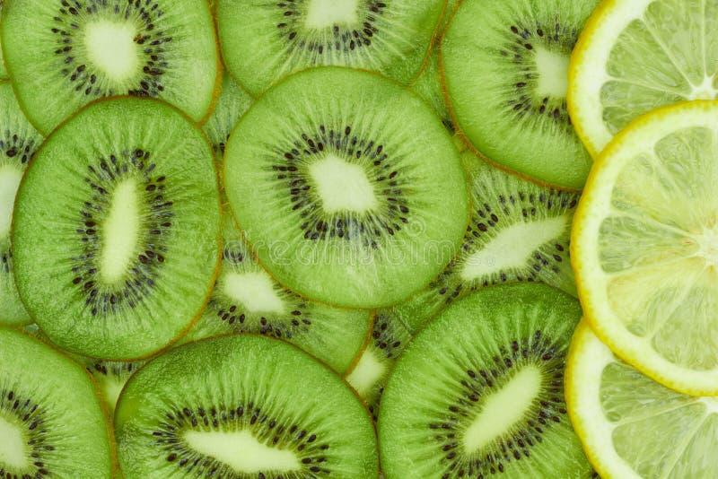 A few lemon slices on kiwi slices background royalty free stock image