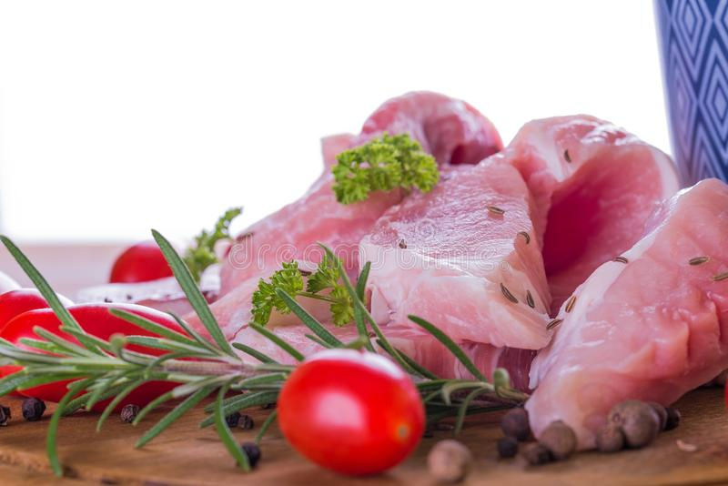 Few long slices of pork meat on wooden board with red tomatoes on white background stock image