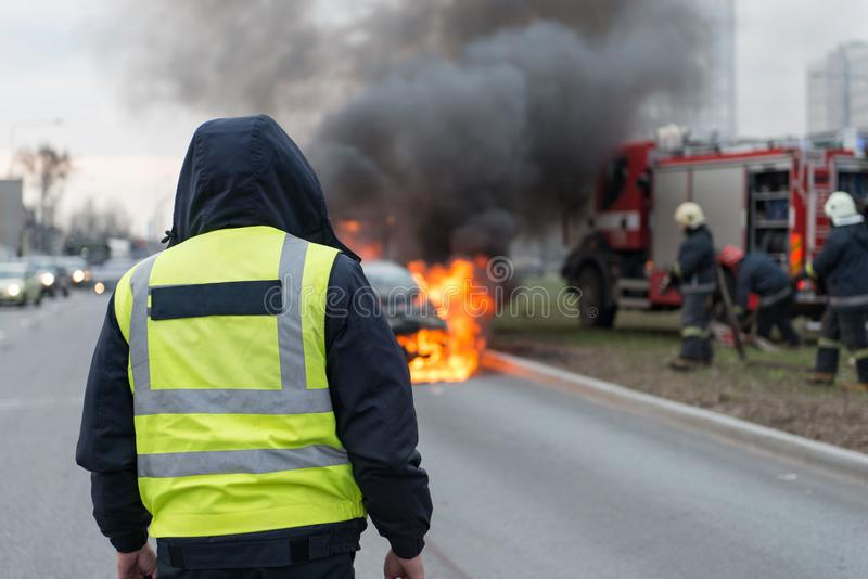 A few minutes in the street burnt car. Traffic is stopped. Firefighters eliminate fire royalty free stock photo