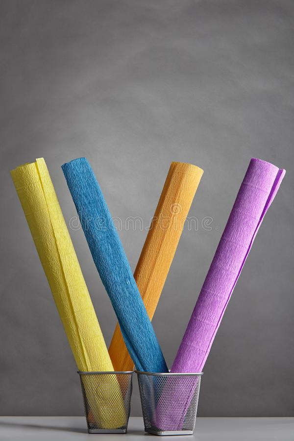 Colorful rolls of wrinkled corrugated paper stand vertical in ba royalty free stock image