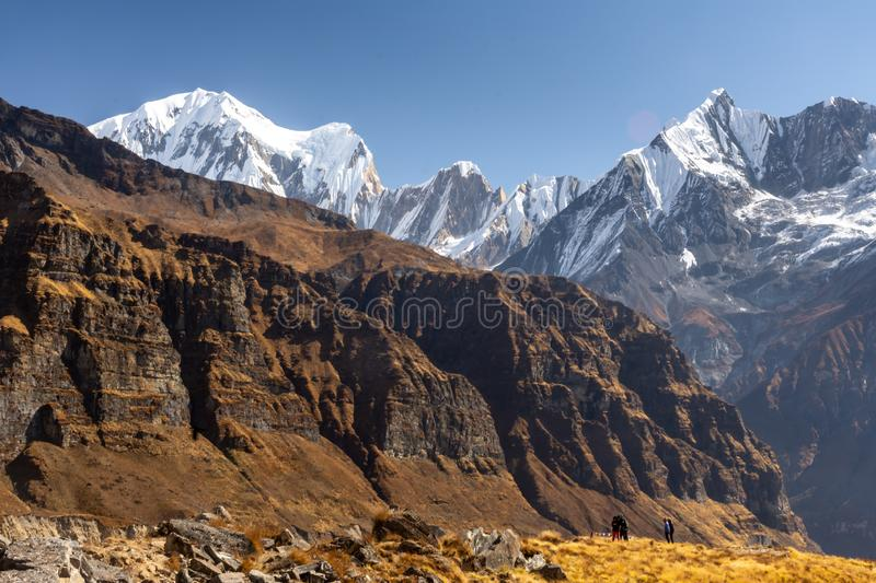 Few nepali men in front of Fish Tail Machapuchare, Himalayas royalty free stock photo
