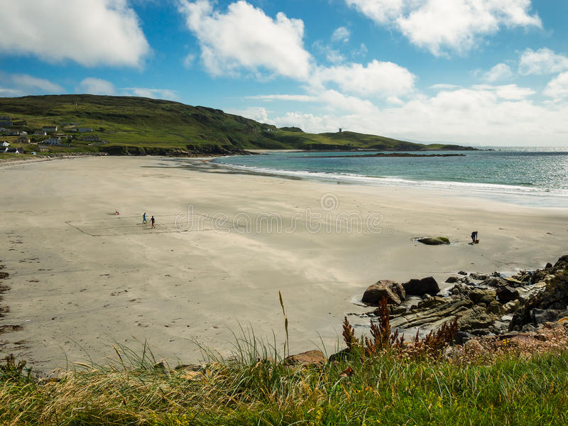 Few people on the beach at Maghery, Donegal. Empty beach with view over the coastal hills near Maghery, County Donegal, Ireland stock photos