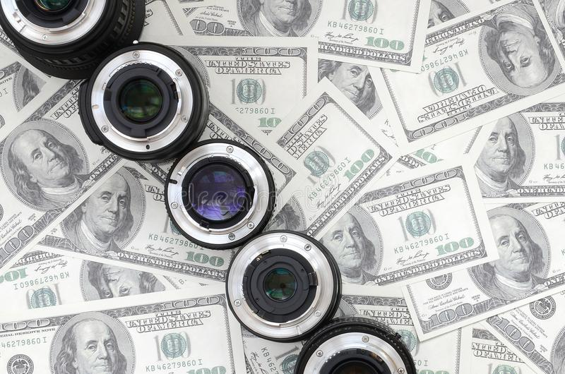 A few photographic lenses lies on the background of a lot of dol stock images