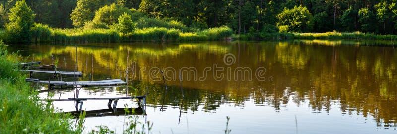 Few połów platformy na forrest jeziorze lub mosty dokąd drzewa odbijają w wodnym, panoramicznym tle, obraz stock