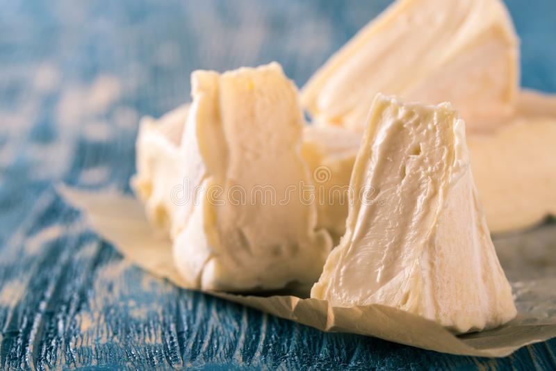 Few portions of camembert cheese on blue wooden board. Horizontal photo of several portions of camembert. Cheese is cut to smaller triangles which are placed stock photo