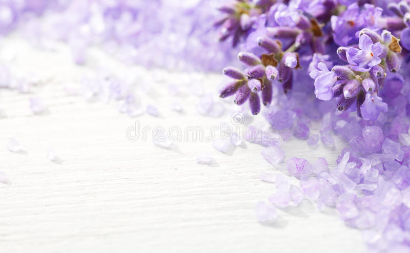 Few sprigs of lavender and mineral bath salts on the wooden table. Shallow DOF. Selective focus stock image