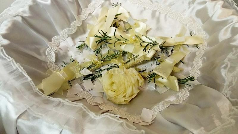 A few twigs of rosemary pinned to the festive wedding bows. The jewelry lies with a white rose in a basket on a silk decorative stock photos