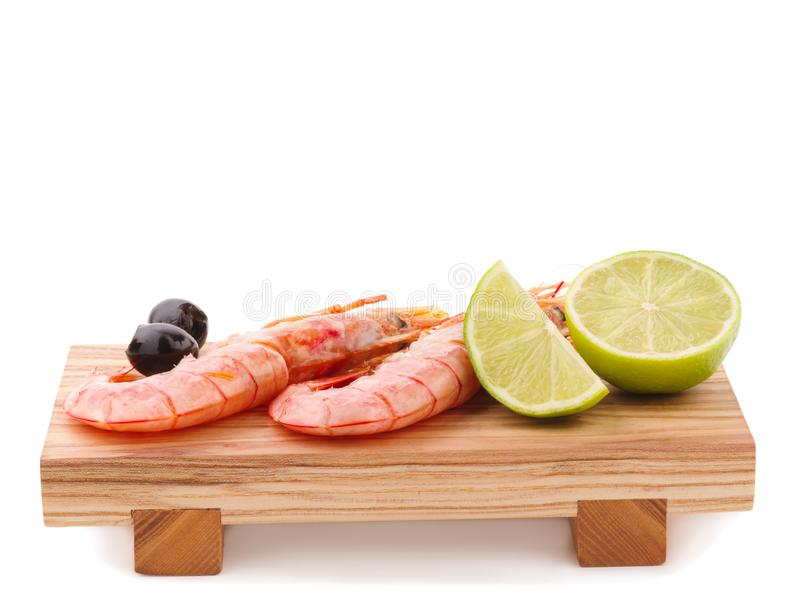 A few unpeeled royal prawns, black olives and a slice of lime. Isolated on white. Close-up. royalty free stock images