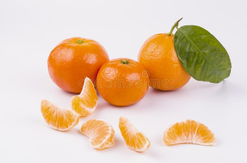 A few whole-tangled tangerines with slices stock image