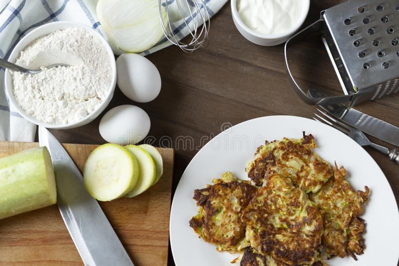Zucchini pancakes on a white plate, sour cream on a brown wooden background, knife, eggs, pieces, fresh, raw, whisk, flour, onion royalty free stock image