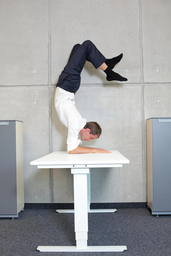 Fexible business man in scorpion asana on electric height adjustable desk. In office  - profile view  - short break royalty free stock images