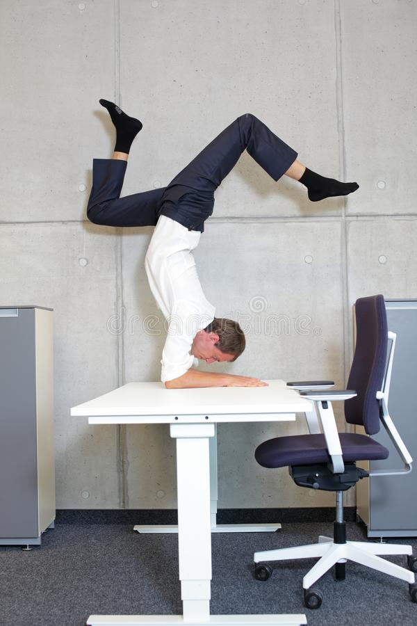 Fexible business man in scorpion asana on electric height adjustable desk. In office  - profile view  - short break royalty free stock image