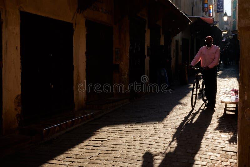 Fez, Maroc - 7 décembre 2018 : Monsieur marocain descendant une vieille rue en Médina de Fez avec une bicyclette image stock