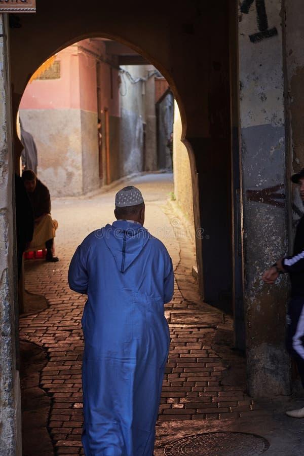 Fez Marocko - December 07 2018: Iklädda blått för marockansk hög gentleman som går till och med en passage i medinaen av fez fotografering för bildbyråer