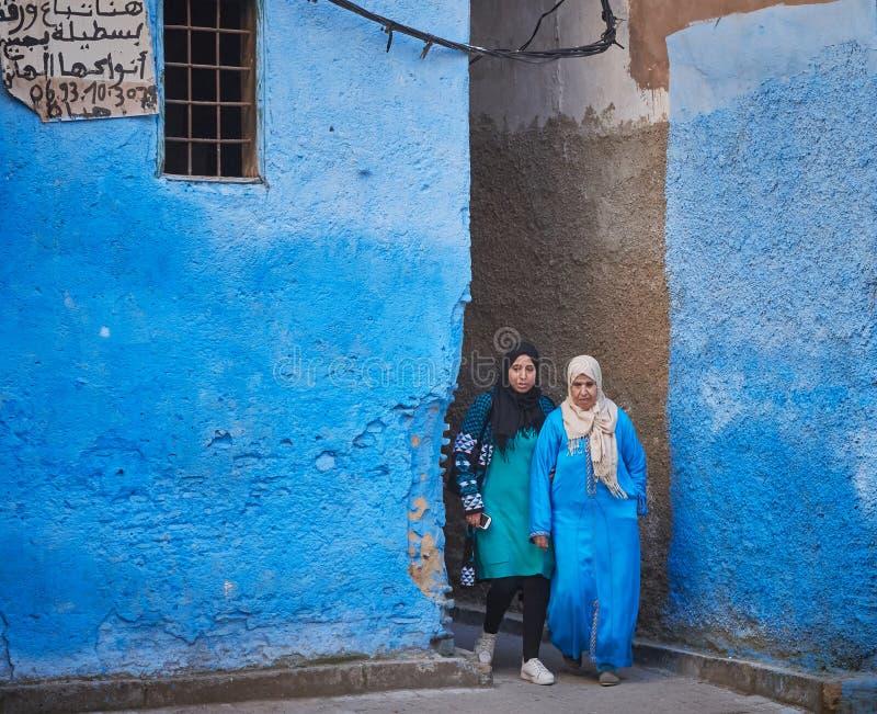 Fez Marocko - December 07, 2018: par av marockanska kvinnor som lämnar en blå gränd i medinaen av fez arkivbild