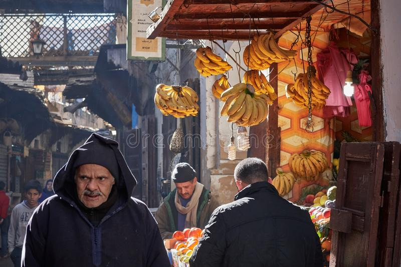 Fez, Marokko - December 07, 2018: Marokkaanse mens die in medina van Fez naast een banaanopslag lopen royalty-vrije stock afbeelding