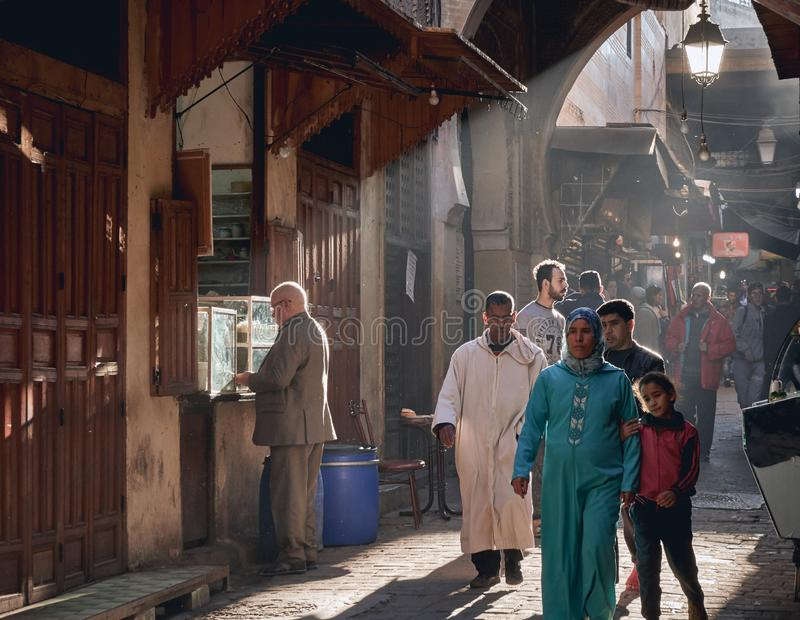 Fez, Marokko - 7. Dezember 2018: Marokkanische Dame mit ihrer Tochter, die durch einen Durchgang des Fez Medina mit Strahlen des  stockbild