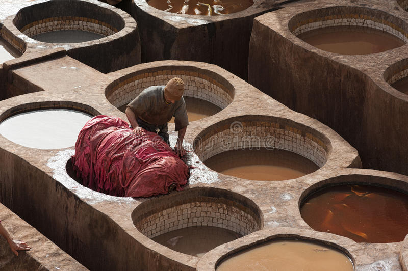 FEZ, MOROCCO - FEBRUARY 20, 2017: Man working within the paint holes at the famous Chouara Tannery in the medina of Fez. stock photos