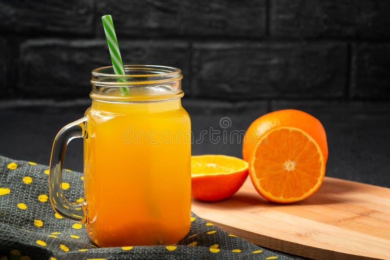 Fez recentemente o suco do citrino das laranjas em uma frasco-caneca com uma palha na tabela cinzenta foto de stock