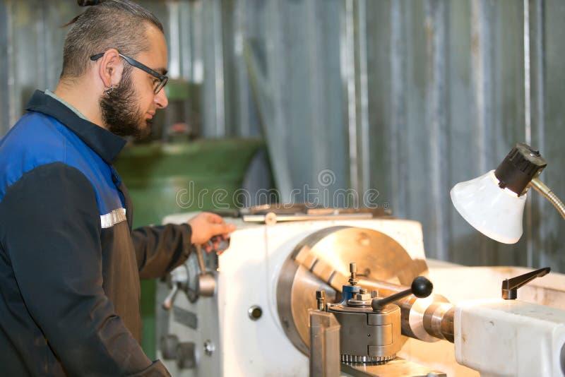 Ffactory manarbetare som arbetar på drejbänkmaskinen arkivbild