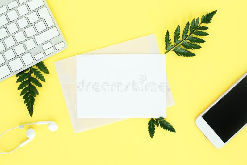 Fflatley på gul bakgrund med tangentbordet, smartphonen, hörlurar och ormbunkesidor, royaltyfria foton