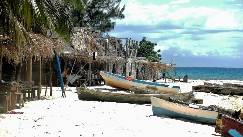 FHand schnitzte Fischerboote auf dem weißen Sandstrand in Roatan stockfotografie
