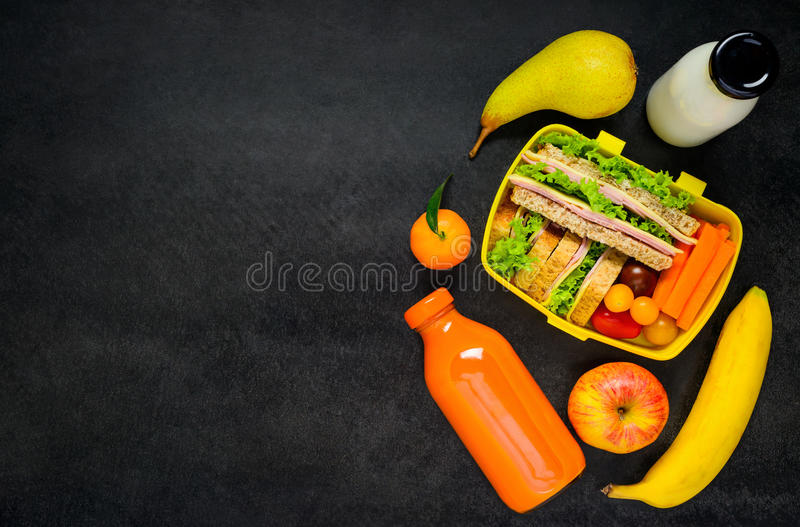 Fiambrera amarilla con las frutas y la leche en espacio de la copia imagen de archivo libre de regalías