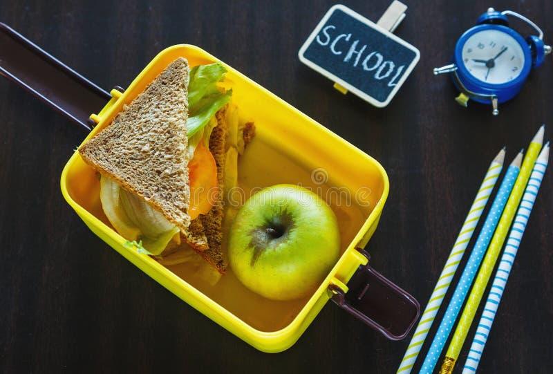 Fiambrera amarilla de la escuela con el bocadillo, manzana verde, lápices, reloj en la pizarra negra Consumición sana en la escue fotos de archivo libres de regalías