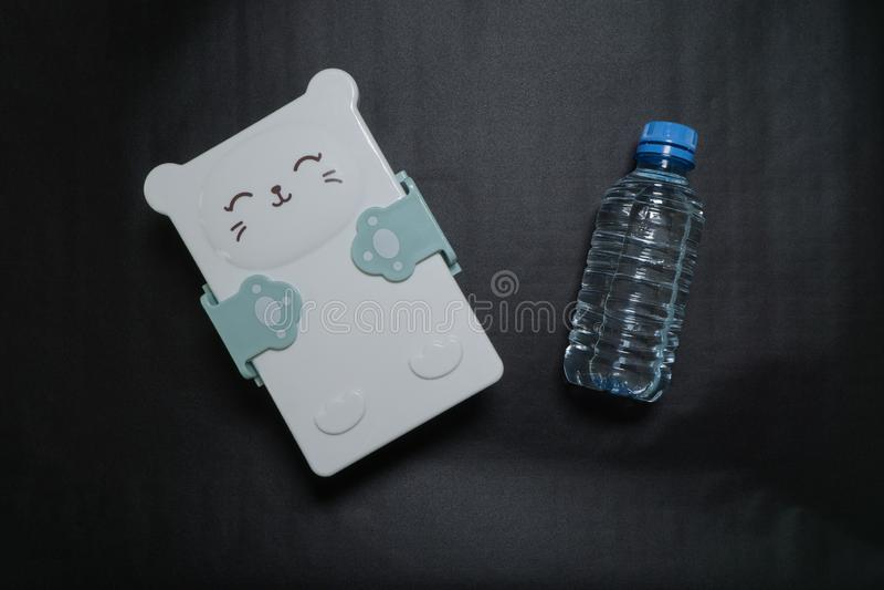 Fiambrera cerrada con un bozal lindo y una botella de agua en un fondo negro imagen de archivo