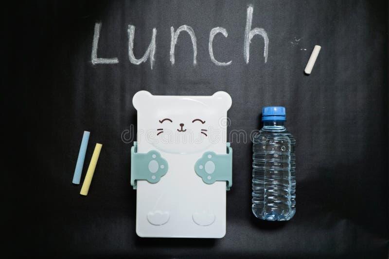 Fiambrera cerrada con un bozal lindo y una botella de agua en un fondo negro con los creyones coloreados y el almuerzo de la insc imagen de archivo libre de regalías
