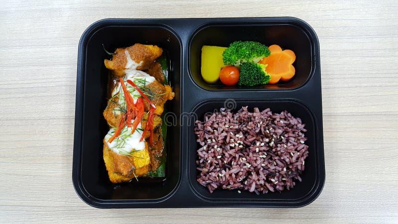 Fiambrera con la baya del arroz, verduras, pollo, calabaza, zanahoria, tomate, patata, bloque kerry en la fiambrera negra, comida foto de archivo libre de regalías