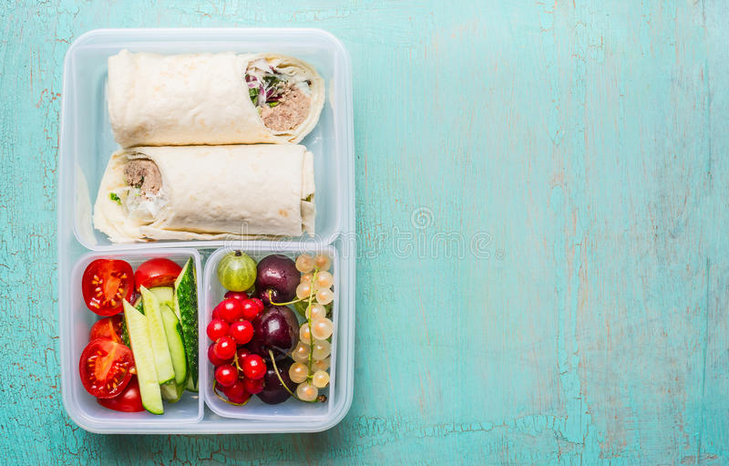 Fiambrera sana con los abrigos de la tortilla del atún, frutas y verduras imagen de archivo