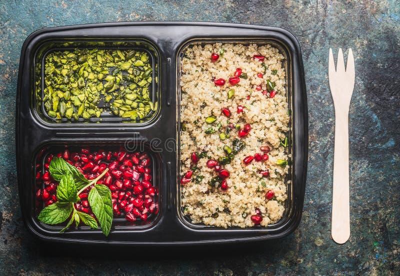 Fiambrera vegetariana sana con la ensalada de la quinoa con la granada y el pistacho fotos de archivo libres de regalías