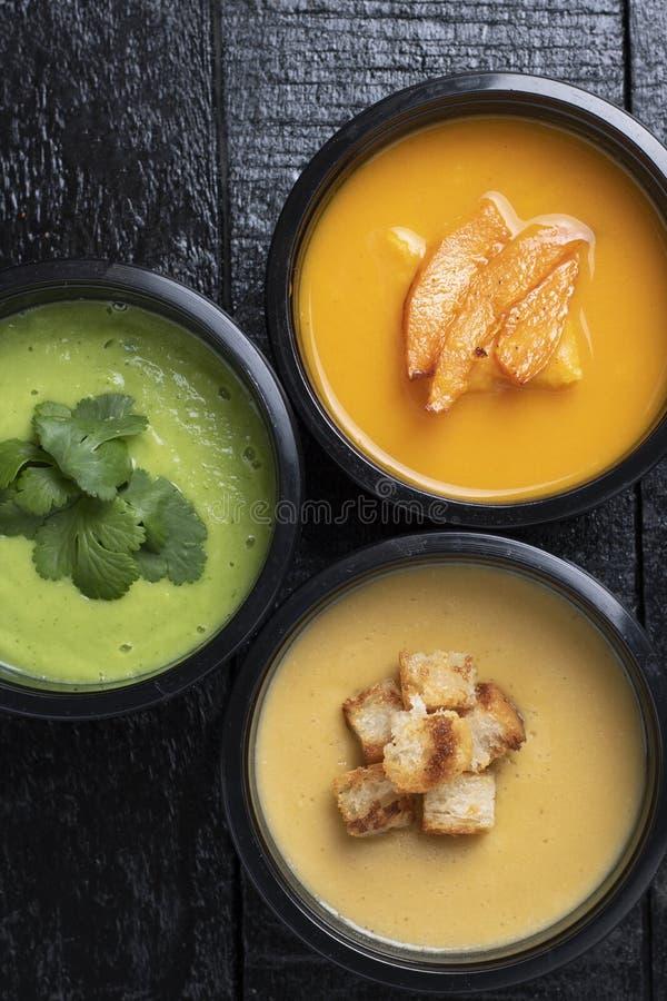 Fiambreras con avacado, la calabaza, la sopa de guisantes, la zanahoria y la pimienta en el tablero de la cocina, lugar para el t fotos de archivo