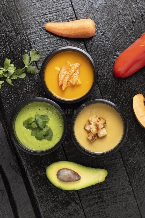 Fiambreras con avacado, la calabaza, la sopa de guisantes, la zanahoria y la pimienta en el tablero de la cocina, lugar para el t fotografía de archivo libre de regalías